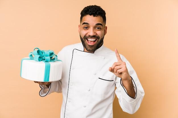 Junger lateinischer bäckermann, der einen kuchen lokalisiert hält, der eine idee, inspirationskonzept hat.