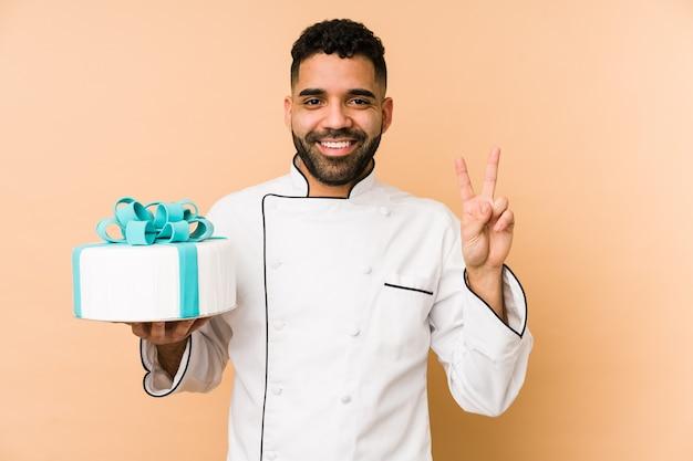 Junger lateinischer bäckermann, der einen kuchen lokalisiert hält, der nummer zwei mit den fingern zeigt