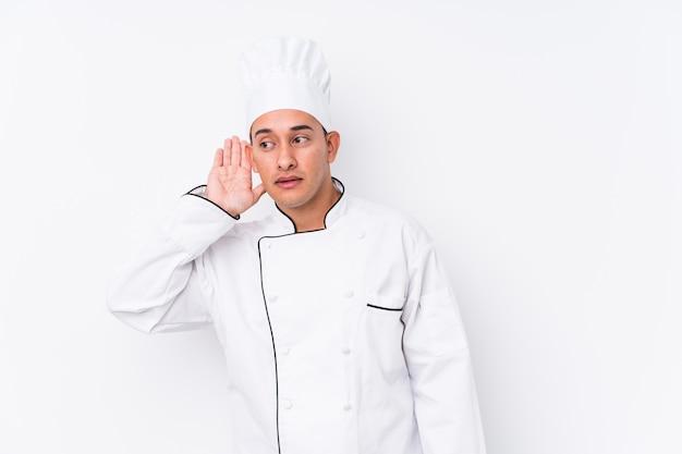 Junger lateinischer chefmann lokalisiertes versuchen, einen klatsch zu hören.