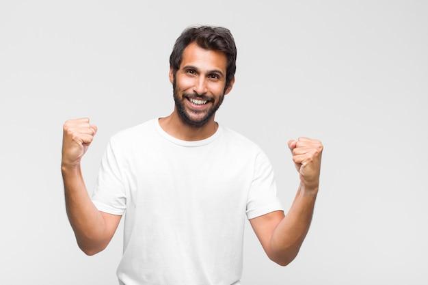 Junger lateinischer gutaussehender mann, der glücklich und freundlich schaut, lächelt und ihnen mit einer positiven einstellung ein auge zuzwinkert