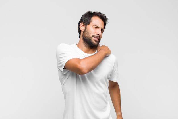 Junger lateinischer gutaussehender mann, der sich müde, gestresst, ängstlich, frustriert und depressiv fühlt und unter rücken- oder nackenschmerzen leidet
