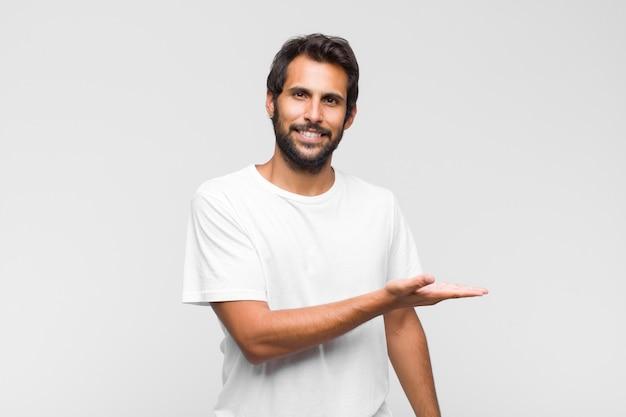 Junger lateinischer hübscher mann, der fröhlich lächelt, sich glücklich fühlt und ein konzept im kopienraum mit handfläche zeigt