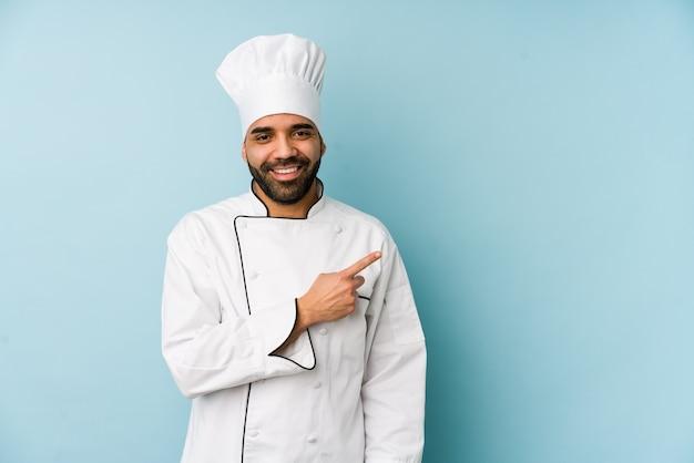 Junger lateinischer kochmann, der lächelt und beiseite zeigt
