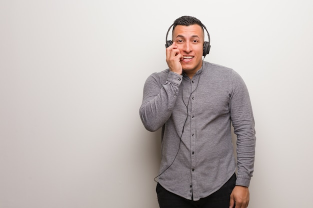 Junger lateinischer mann, der auf die beißenden nägel der musik, nervös und sehr besorgt hört