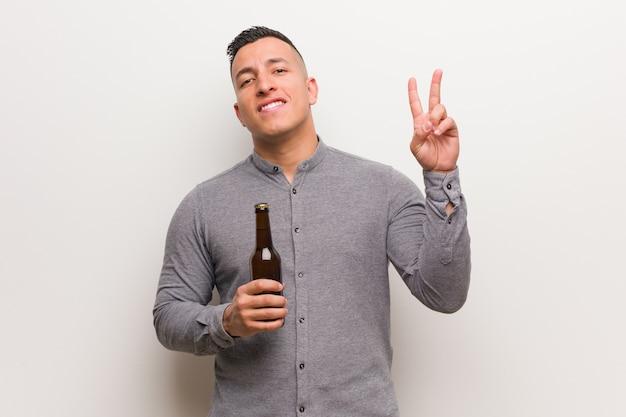 Junger lateinischer mann, der ein bier zeigt nummer zwei hält