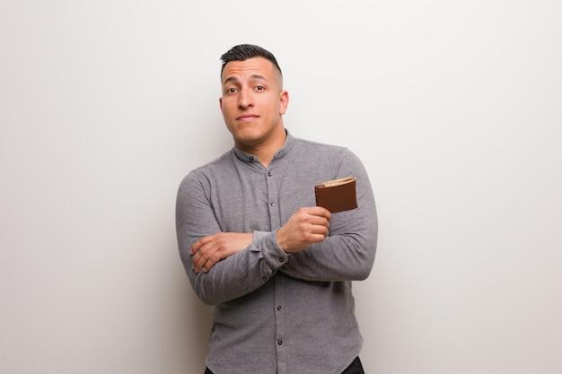 Junger lateinischer mann, der ein geldbörsenlächeln überzeugt hält und die arme, oben schauend kreuzt