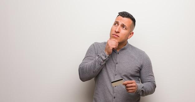 Junger lateinischer mann, der eine kreditkarte zweifelhaft und verwirrt hält