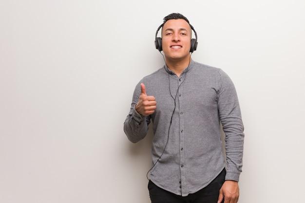 Junger lateinischer mann, der musik lächelt und oben daumen anhebt hört