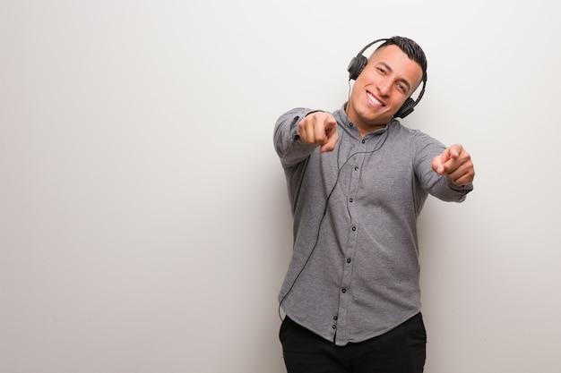 Junger lateinischer mann, der musik nett hört und auf front zeigt