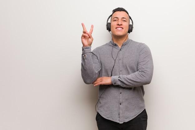 Junger lateinischer mann, der musik zeigt nummer zwei hört