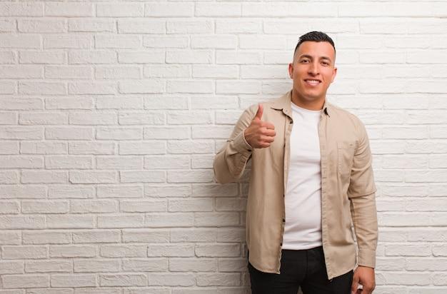 Junger lateinischer mann, der oben daumen lächelt und anhebt