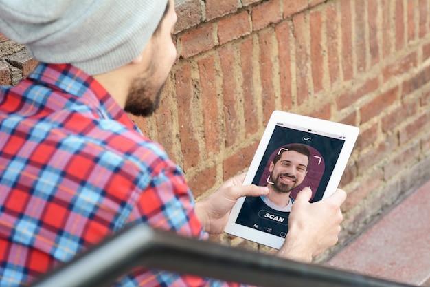 Junger lateinischer mann, der smartphone mit gesichtserkennungstechnologie entsperrt