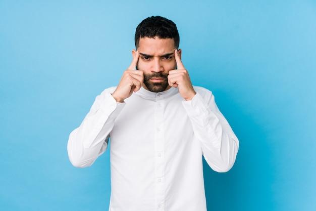 Junger lateinischer mann gegen eine blaue lokalisierte wand konzentrierte sich auf eine aufgabe und hielt die zeigefinger, die kopf zeigen.