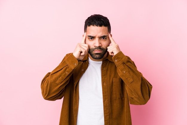 Junger lateinischer mann gegen eine rosa lokalisierte wand konzentrierte sich auf eine aufgabe und hielt die zeigefinger, die kopf zeigen.