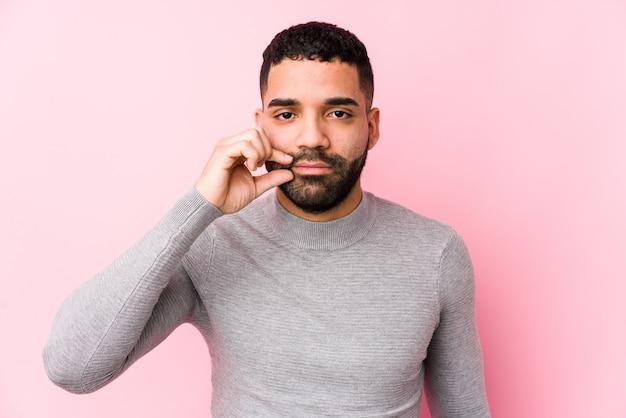 Junger lateinischer mann gegen eine rosa wand lokalisiert mit den fingern auf den lippen, die ein geheimnis halten.