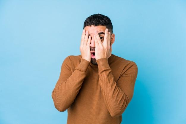 Junger lateinischer mann gegen einen blauen lokalisierten hintergrund blinken durch die erschrockenen und nervösen finger.