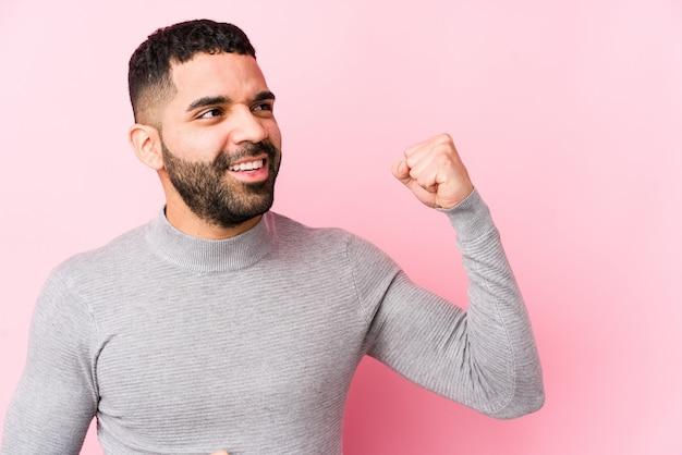 Junger lateinischer mann gegen rosa