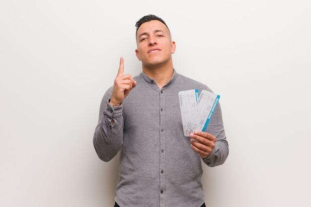 Junger lateinischer mann, halten flugtickets, die nummer eins zeigen