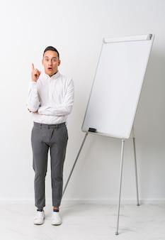 Junger lateinischer trainermann mit einem whiteboard lokalisierte das haben irgendeiner großartigen idee, konzept der kreativität.