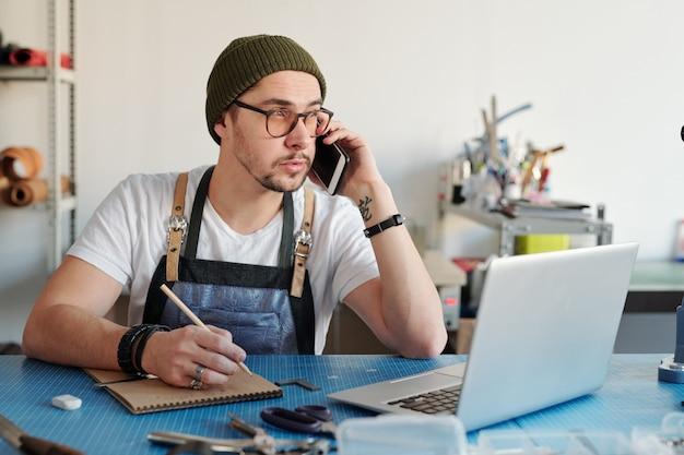 Junger lederarbeiter, der mit dem kunden per handy spricht, während er über skizze des neuen artikels vor laptop arbeitet