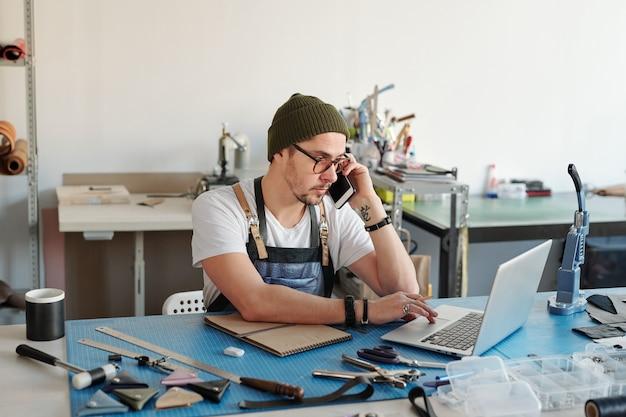 Junger lederarbeiter im mützenhut unter verwendung des laptops beim anrufen des kunden am telefon, um lederprodukt zu besprechen