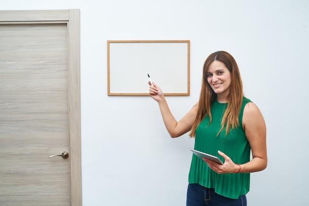 Junger lehrer, der auf ein whiteboard zeigt. konzept des studiums, des unterrichts und des neuen kurses.