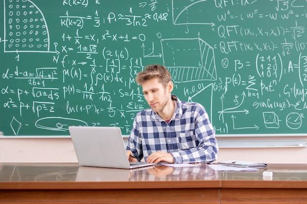 Junger lehrer, der mit laptop arbeitet oder ein online-vorlesungswebinar gibt