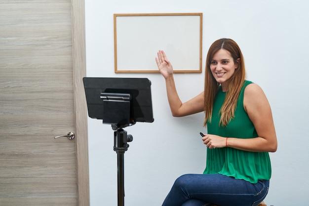 Junger lehrer, der online-klassen zu hause per videoanruf gibt.