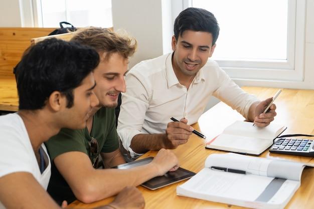 Junger lehrer, der zwei studenten über firmenbudgetierung erzählt