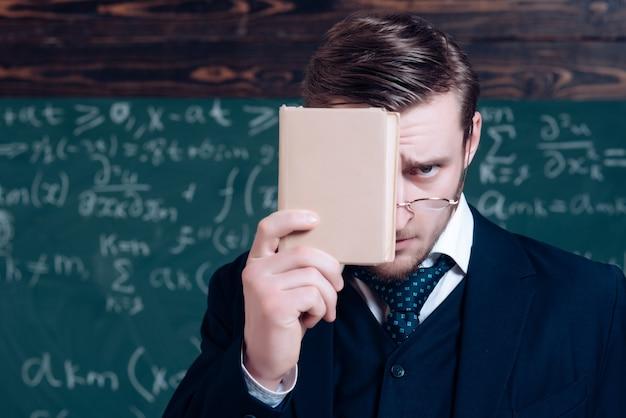 Junger lehrer im anzug, der sein gesicht mit buch bedeckt. nahaufnahmeporträt des jungen professors.