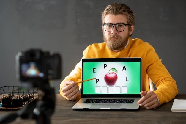 Junger lehrer im gelben pullover, der online-aufgabe für seine schüler beim sitzen am tisch vor laptop in der häuslichen umgebung macht