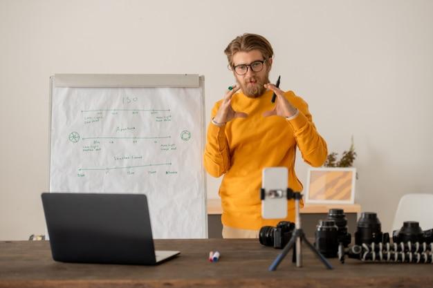 Junger lehrer in freizeitkleidung, der auf schriftliche informationen auf dem whiteboard zeigt, während er sie seinem publikum während des online-unterrichts erklärt