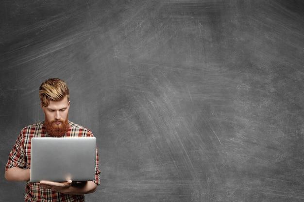 Junger lehrer mit stilvollem bart gekleidet im roten flanellhemd, das auf laptop-computer im klassenzimmer nach unterricht arbeitet.