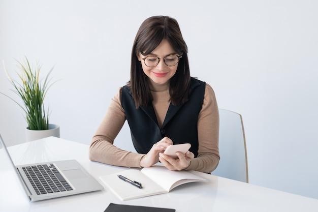 Junger lehrer oder geschäftsfrau mit smartphone über offenem heft, das den kontakt beim sitzen am schreibtisch vor laptop sucht