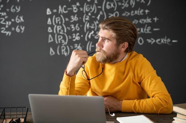 Junger lehrer oder schüler in freizeitkleidung, der laptop-anzeige während der online-algebra-lektion betrachtet, während er seine hände auf dem hinterkopf hält