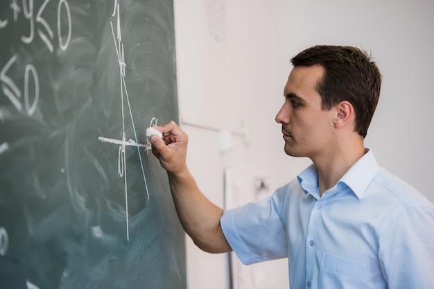 Junger lehrer oder schüler zeichnen dreieck auf einer tafel mit formel