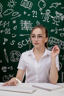 Junger lehrer sitzt nahe tafel im klassenzimmer