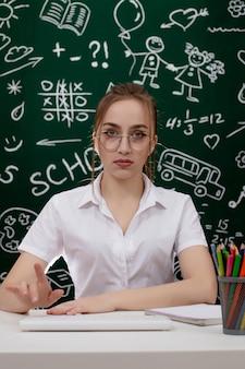 Junger lehrer sitzt nahe tafel im klassenzimmer.