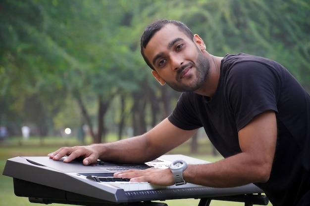 Junger leidenschaftlicher mann, der e-piano spielt stockfoto