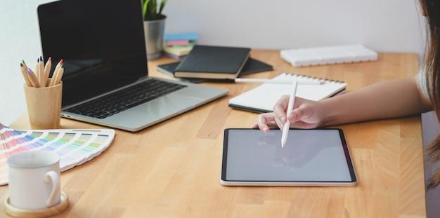 Junger leidenschaftlicher weiblicher freiberufler, der ihre idee auf tablette schreibt