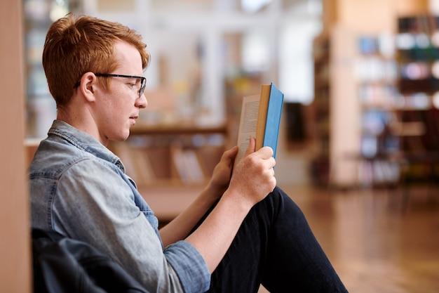 Junger leser in freizeitkleidung, der durch bücherregal in der bibliothek sitzt, während er interessantes buch liest
