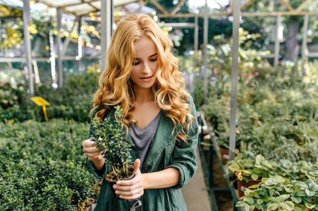 Junger liebhaber der flora geht durch botanischen garten. nettes blondes mädchen betrachtet pflanzen mit interesse.