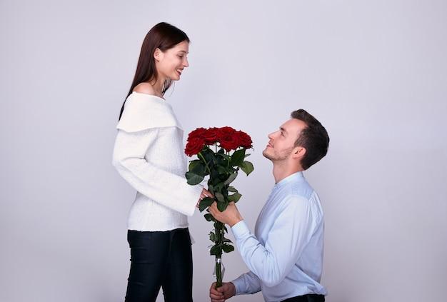Junger liebhaber erhält rote rosen von einem mann.