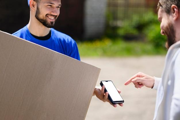 Junger lieferbote, der auf kunden wartet, um sendung zu bestätigen