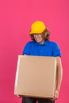 Junger lieferbote, der blaues poloshirt und gelbe kappe trägt, die großen großen schweren pappkarton hält, der sich wegen des schweren gewichts über lokalisiertem rosa hintergrund unwohl fühlt