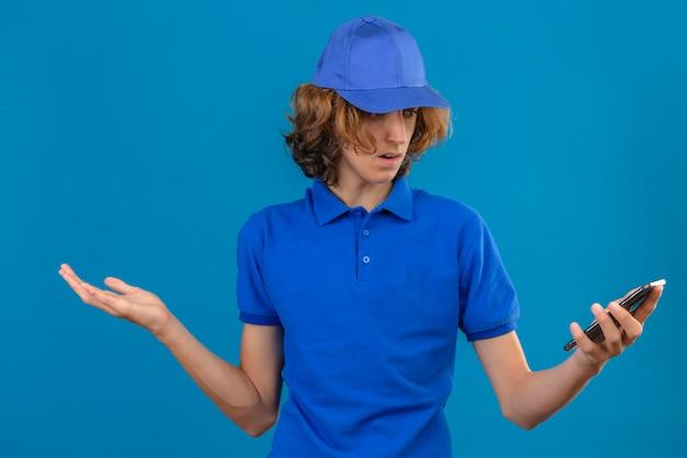 Junger lieferbote, der blaues poloshirt und kappe ahnungslos trägt und mit offenen armen verwechselt keine ahnung konzept steht über isoliertem blauem hintergrund