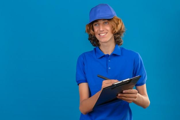 Junger lieferbote, der blaues poloshirt und kappe hält, die zwischenablage hält, die etwas schreibt, während fröhlich über lokalisierten blauen hintergrund lächelt