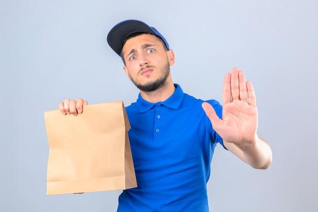 Junger lieferbote, der blaues poloshirt und kappe hält papiertüte mit essen zum mitnehmen, das besorgt schaut, stoppgeste mit hand über lokalisierten weißen hintergrund macht