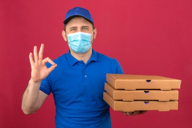 Junger lieferbote, der blaues poloshirt und kappe in der medizinischen maske hält, die stapel von pizzaschachteln hält ok zeichen mit glücklichem gesicht über lokalisiertem rosa hintergrund zeigt