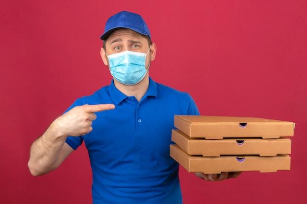 Junger lieferbote, der blaues poloshirt und kappe in der medizinischen maske hält, die stapel von pizzaschachteln zeigt, zeigt finger auf sie, die kamera mit lächeln stehend über lokalisiertem rosa hintergrund stehen